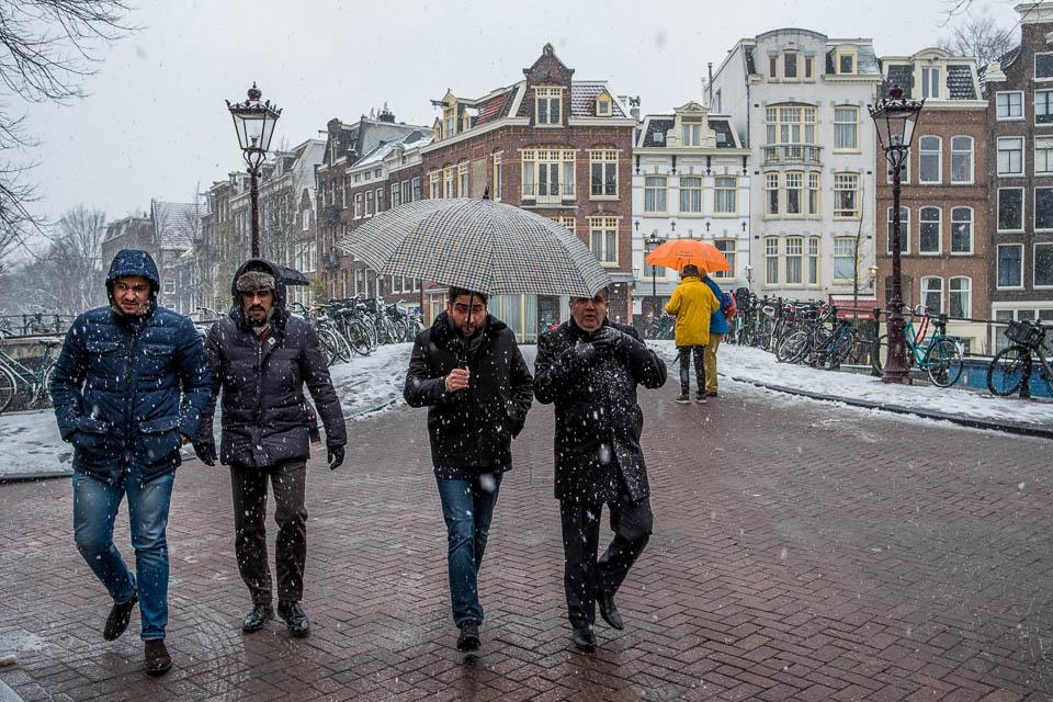 Amsterdam straatfoto, Prinsengracht, mannen met paraplu in de sneeuw.