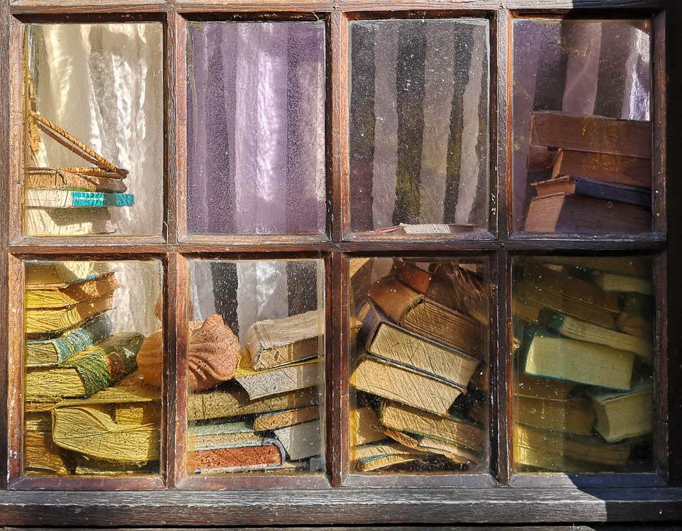 Duitsland, Monschau in de Eifel. Stapel oude boeken achter kleurrijke ramen. Smartphone Huawei P20 Pro.