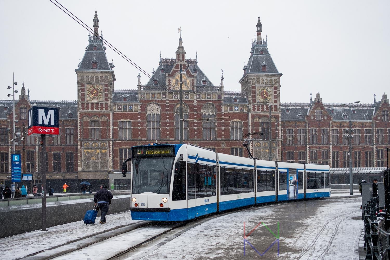 Amsterdam Centraal Station in de sneeuw met reiziger met rolkoffer en een passerende tram