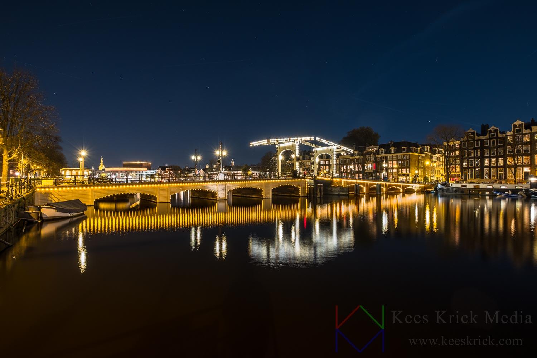 Amsterdam Amstel en de Magere Brug op een heldere en windstille winteravond. Uniek! Standpunt vanaf het water.