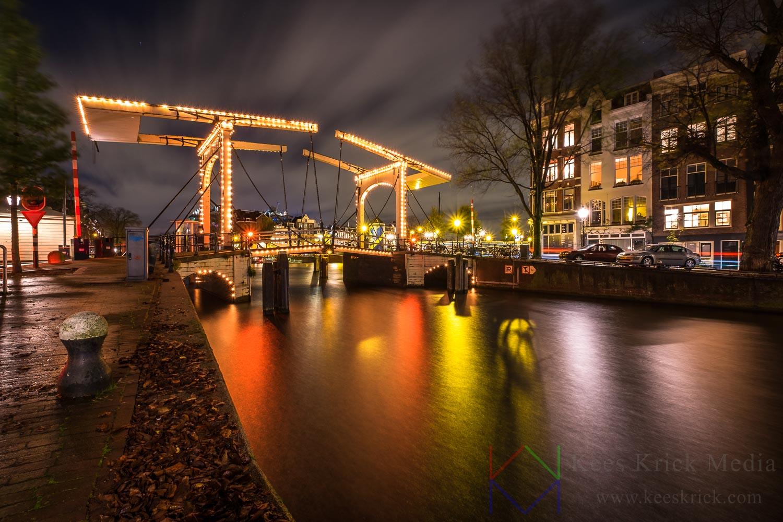 Amsterdam Amstel en verlichte boogbrug over de Nieuwe Herengracht tijdens een zware storm.