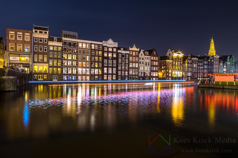 Amsterdam Damrak met lichtspoor van een rondvaartboot.
