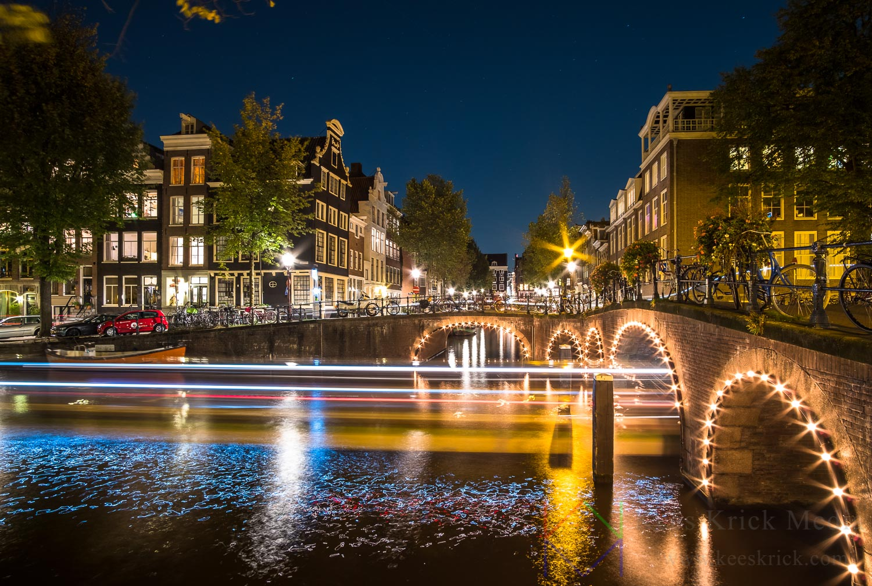 Amsterdam Herengracht en Blauwburgwal met verlichte boogbruggen en grachtenpanden tijdens volle maan. Met lichtspoor van rondvaartboot.