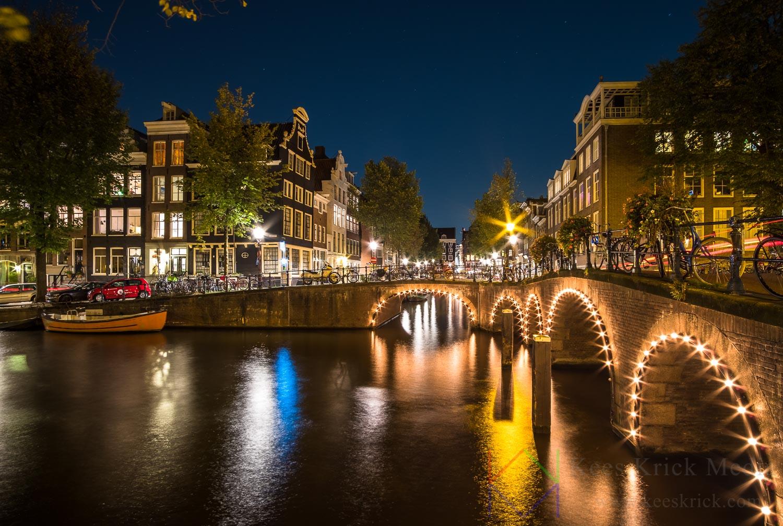 Amsterdam Herengracht en Blauwburgwal met verlichte boogbruggen en grachtenpanden tijdens volle maan.