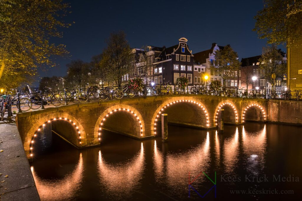 Amsterdam Herengracht en Blauwburgwal met verlichte boogbruggen en grachtenpanden.