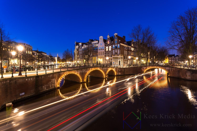 Amsterdam Keizersgracht en Leidsegracht met verlichte boogbruggen en grachtenpanden tijdens het blauwe uur.  Met lichtstrepen van een passerende rondvaartboot.