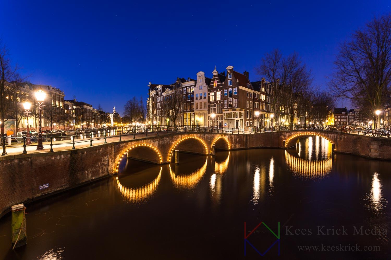 Amsterdam Keizersgracht en Leidsegracht met verlichte boogbruggen en grachtenpanden tijdens het blauwe uur.