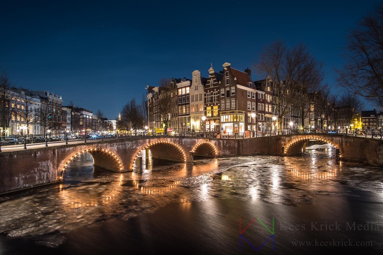 Amsterdam Keizersgracht en Leidsegracht met verlichte boogbruggen en grachtenpanden tijdens volle maan.  De grachten zijn bevroren (winter 2017-2018).