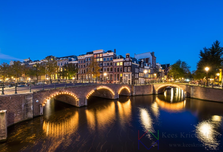 Amsterdam Reguliersgracht en Keizersgracht tijdens het blauwe uur. Met verlichte boogbruggen en grachtenpanden.