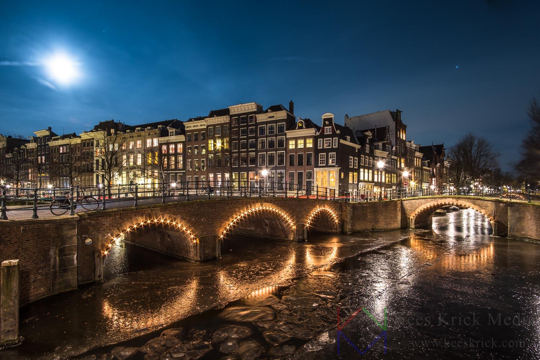 Amsterdam Reguliersgracht en Keizersgracht tijdens volle maan. Met verlichte boogbruggen en grachtenpanden. De grachten zijn bevroren (winter 2017-2018).