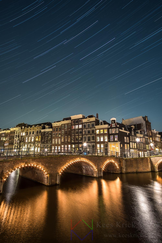 Sterrenhemel boven Amsterdam Reguliersgracht en Keizersgracht tijdens nieuwe maan. Met verlichte boogbruggen en grachtenpanden. Sterrensporen zijn ontstaan door de lange belichting van een uur.