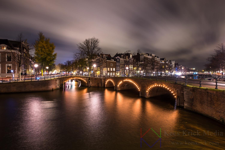 Amsterdam Reguliersgracht en Keizersgracht tijdens een storm. Met verlichte boogbruggen en grachtenpanden.