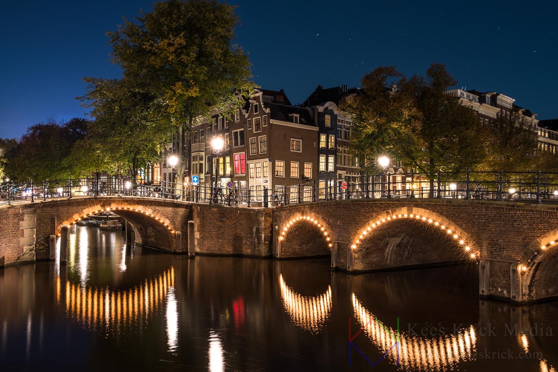 Amsterdam Reguliersgracht en Keizersgracht tijdens volle maan. Met verlichte boogbruggen en grachtenpanden.