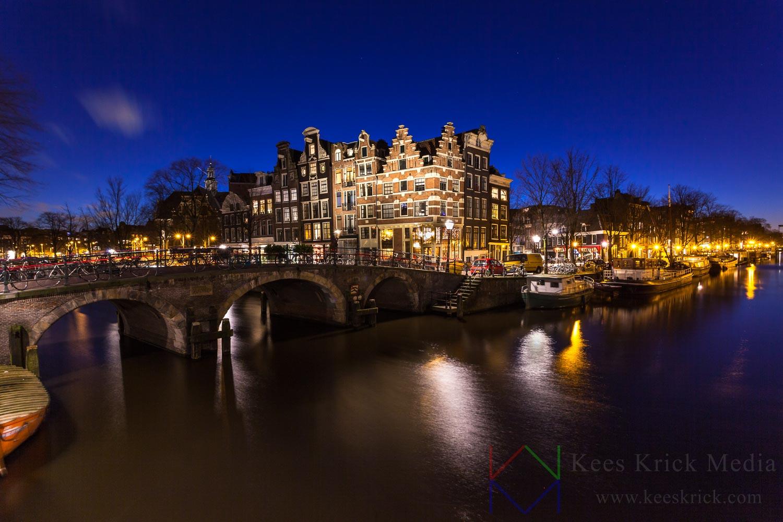 Amsterdam Prinsengracht en Brouwersgracht met boogbruggen en verlichte grachtenpanden tijdens het blauwe uur.