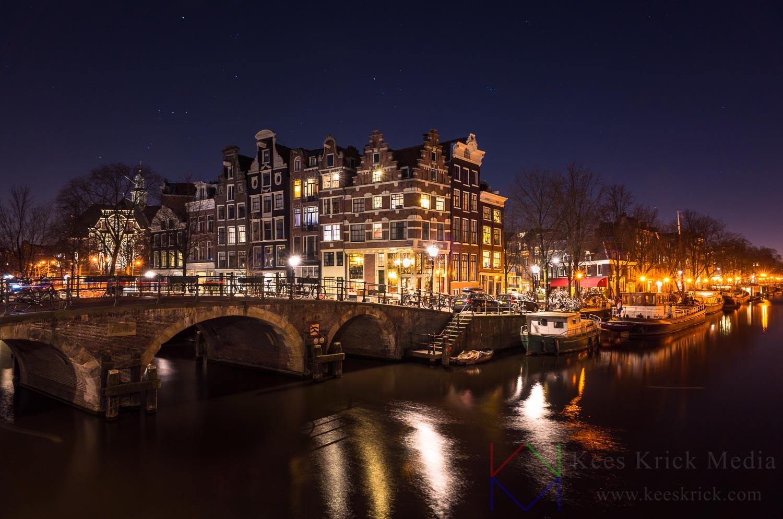 Amsterdam Prinsengracht en Brouwersgracht met boogbruggen en verlichte grachtenpanden.