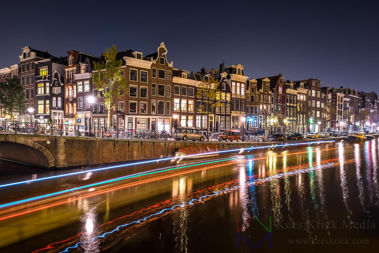 Amsterdam Prinsengracht en Spiegelgracht met verlichte grachtenpanden en spoor van een rondvaartboot.