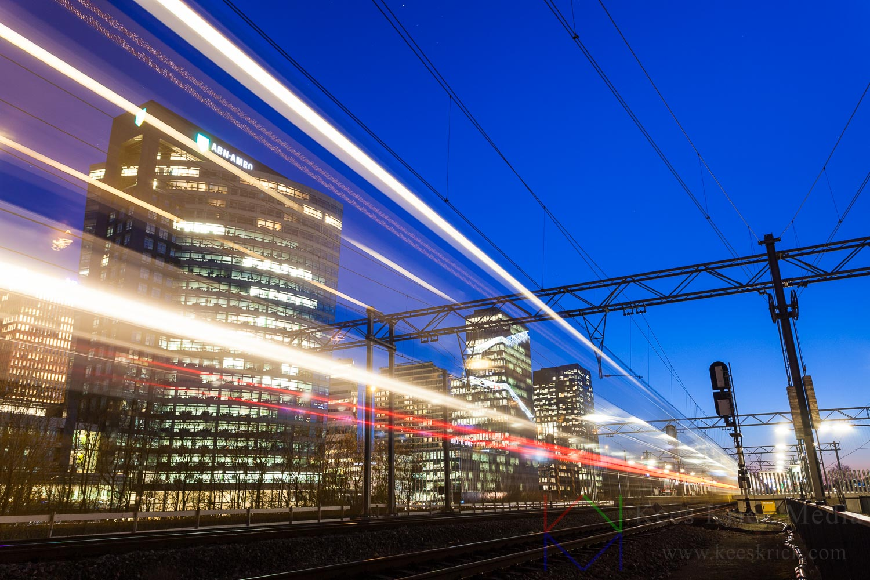 Amsterdam Zuidas skyline tijdens het blauwe uur. Met lichtsporen van een passerende trein.