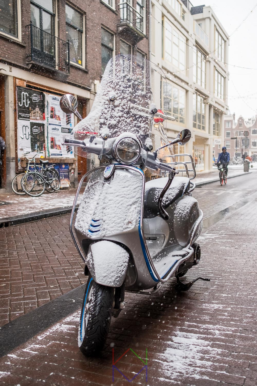 Amsterdam Negen Straatjes met besneeuwde scooter en naderende fietser