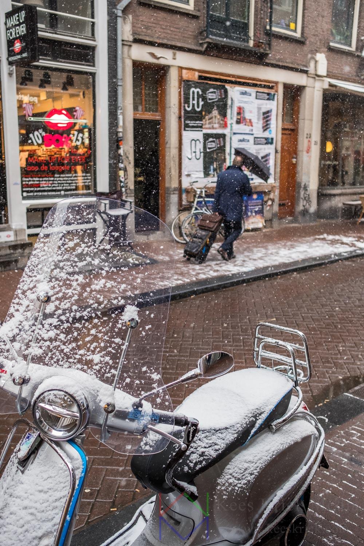 Amsterdam Negen Straatjes met besneeuwde scooter en reiziger met rolkoffer en paraplu