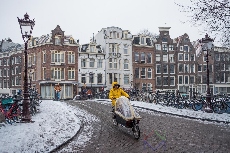 Amsterdam Prinsengracht met fietser in gele regenjas op bakfiets op de brug