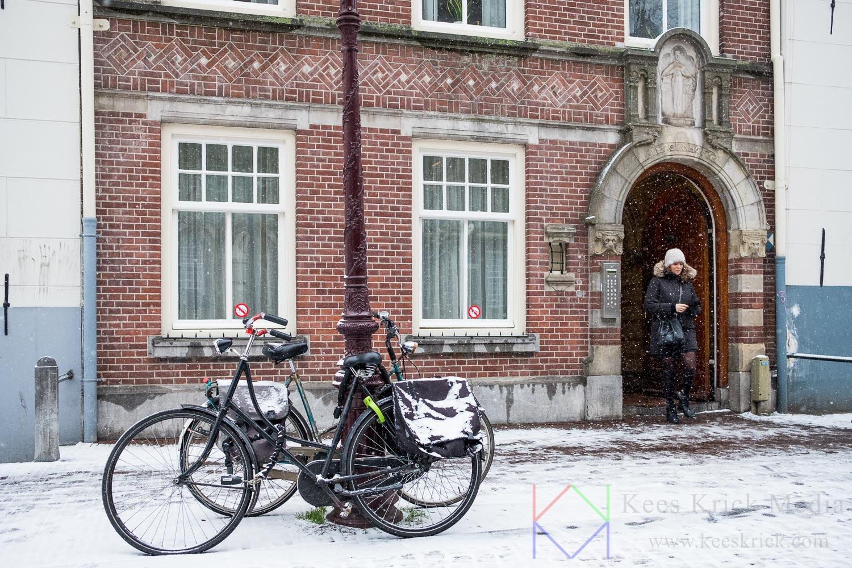 Amsterdam Spui in de sneeuw met fietsen tegen lantaarnpaal geparkeerd en voorbijganger die uit poort van de Begijnhof stapt
