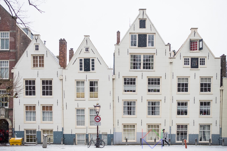 Amsterdam Spui in de sneeuw met witte huisjes van het Begijnhof en een voorbijganger in passende kleuren