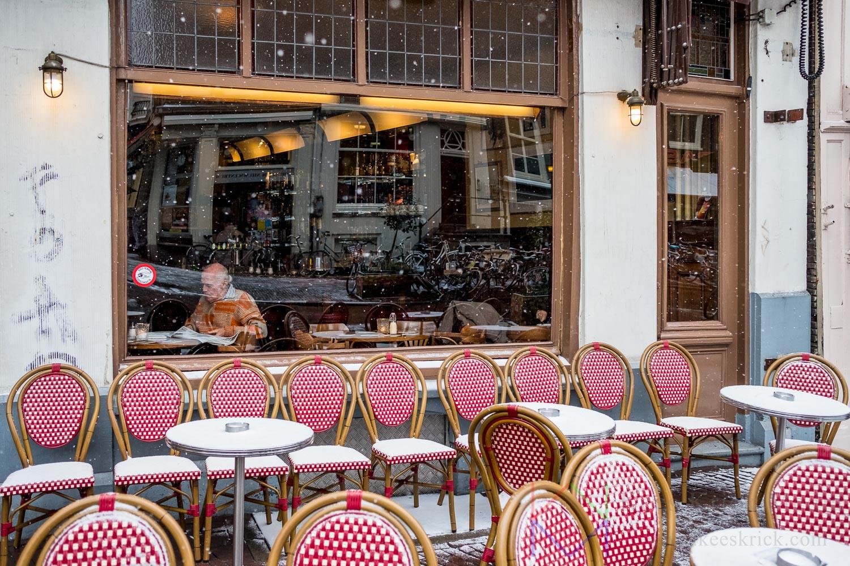 Amsterdam Spui in de sneeuw met achter het raam van een cafe een man die de krant leest en ervoor een leeg terras