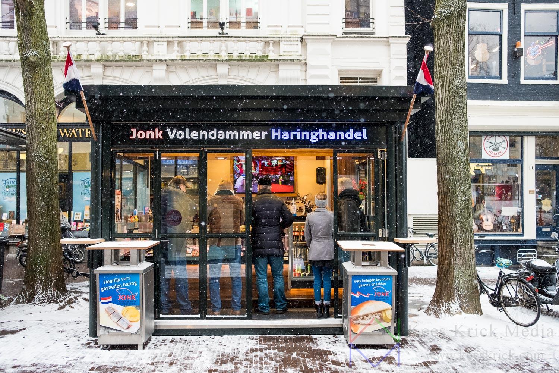 Amsterdam Spui in de sneeuw met publiek bij de haringkar