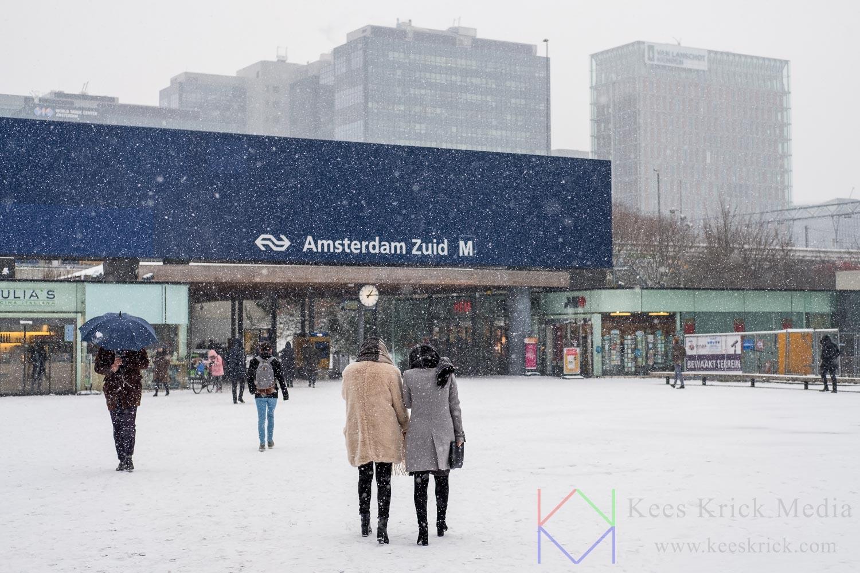 Amsterdam Zuidas bij station Zuid met voorbijgangers in de sneeuw